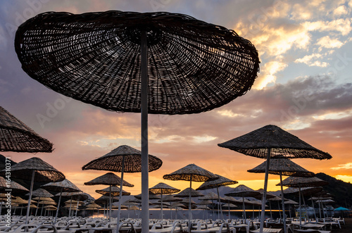 Papiers peints Cappuccino Colorful sunrise on the beach against the background of the sea and the mountains. Rest on the sea. Beach umbrellas and skiers.