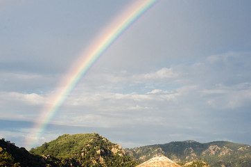 Rainbow in the sky against the background of high rocks and mountains on the beach.