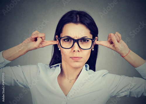 Photo  Angry woman plugging her ears with fingers