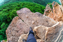 Man Hiker Steps On The Edge Of Mountain Rock Above Precipice With Green Forest Trees Underneath. Caucasus Mountain Summer Scenery. Fisheye View