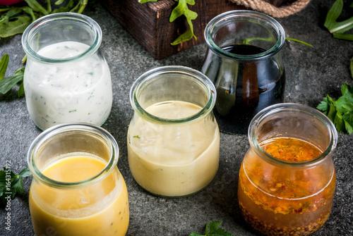 Fotografía  Set of dressings for salad: sauce vinaigrette, mustard, mayonnaise or ranch, balsamic or soy, basil with yogurt