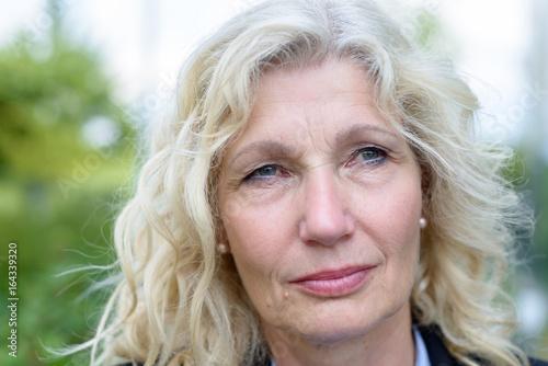 Poster  Senior businesswoman standing thinking deeply