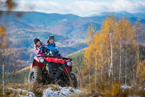 Happy females ATV driver in winter clothing on snowy hills on the background of mighty mountains and trees with yellow leaves. Girl is showing something in distance to her friend. Sunny autumn day