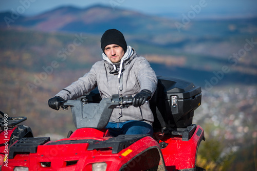Close-up of man in winter clothing on red quad bike looking at the camera on the blurred background at sunny day