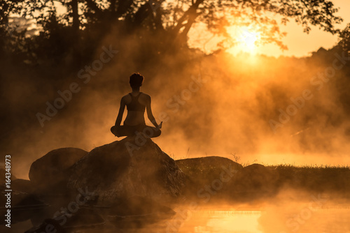 Fotobehang Ontspanning Silhouette of a beautiful Yoga woman in the morning at the hot spring park, soft and select focus