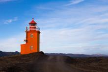 Orange Lighthouse On A Stony Coast In Iceland