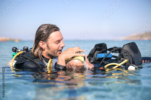 Scuba diver doing a rescue procedure on a girl