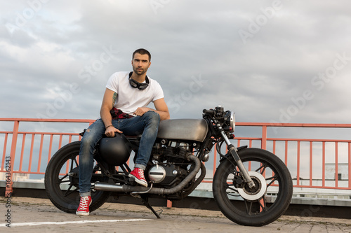 Fotografie, Obraz  Handsome rider man with a beard and mustache sit on classic style biker cafe racer motorcycle and and wait his woman