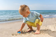 The boy on the beach plays in the sand