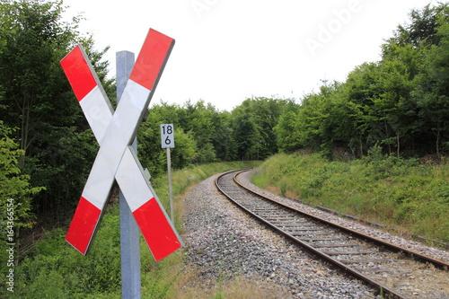 Andreaskreuz mit Blick auf die Bahnschienen, die in einer Rechtskurve verschwinden