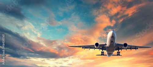 Poster Avion à Moteur Landing airplane. Landscape with white passenger airplane is flying in the blue sky with multicolored clouds at sunset. Travel background. Passenger airliner. Business trip. Commercial aircraft