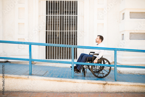 Man in wheelchair going up a ramp Fotobehang