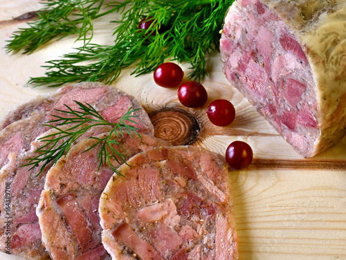 Fotografia Homemade brawn or headcheese with dill and cranberries on a wooden board