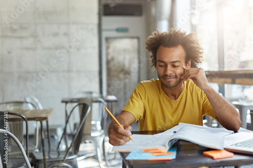 Fototapeta Creative young author with curly hair and dark skin dressed casually sitting at cafeteria preparing for writing new article in his newspaper having gentle smile on his face having good ideas in mind obraz