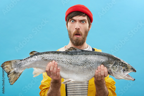 Obraz Headshot of funny emotional young bearded Caucasian fisherman in hat and raincoat holding large salmon in both hands, staring at camera with shocked look, can't believe that he caught such a big fish - fototapety do salonu