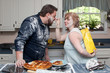 Wife looks mischievous with a bag of flour behind back during a food fight with husband in the kitchen.
