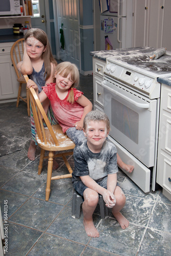 Three naughty children who have just made a mess in the kitchen sit beside the Fotobehang
