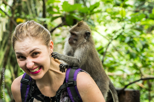 In de dag Aap Woman interacting with a monkey in Bali, Indonesia