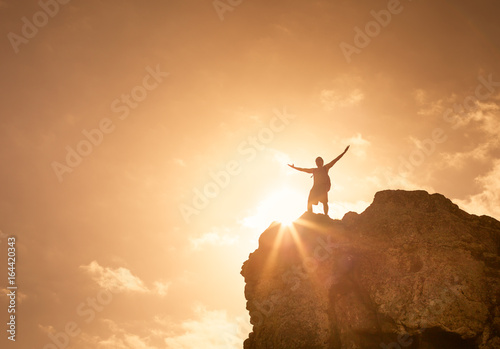 Fotografiet  Man on top a mountain celebrating. Victory and success concept.