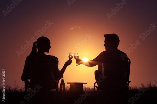 Young couple outdoors enjoying a glass of wine.  Love and relationships.