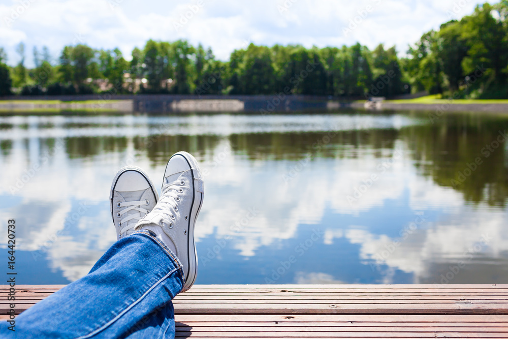 Fototapeta People relaxing in nature. Persons feet relaxing by a beautiful lake.