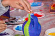Young children decorating handmade clay pottery