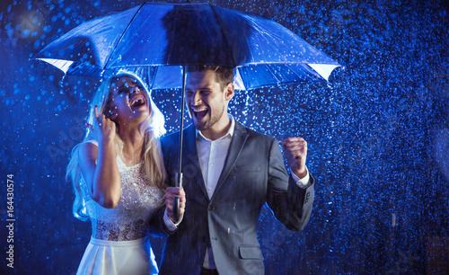 Acrylic Prints Cheerful couple enjoying the summer rain