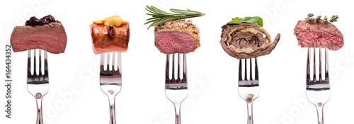 Fleisch vom Wild, Lamm, Rind und Roulade aund Wurst auf einer Gabel - 164434352