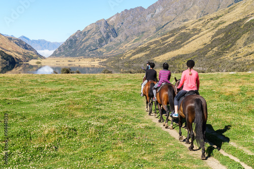 Horse riding in mountains by lake