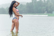 Young beautiful black-haired woman posing on the beach in the water