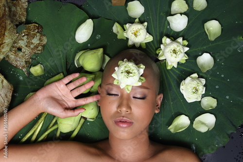 Skin Head Girl on Lotus flower and banana leaf with drop of water, shadow and depth of field