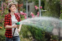 Woman Gardener Watering Garden