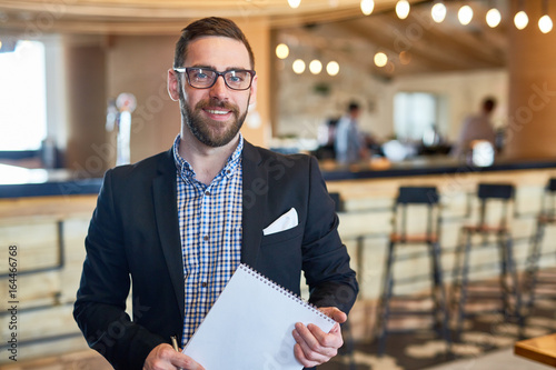 Fotomural Businessman with notepad looking at camera in restaurant