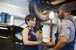 Repair service staff handshaking in workshop