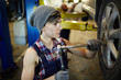 Female technician in overalls fixing car tire with special hand-tool