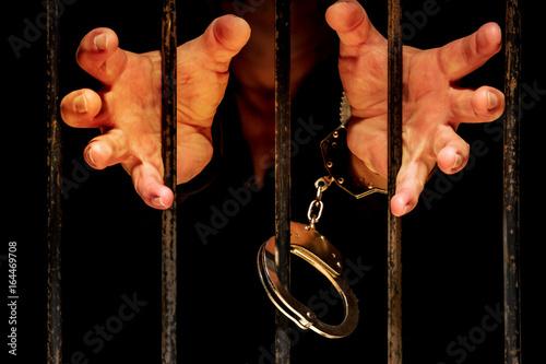 Poster die Hände eines eingesperrten Mannes wollen durch ein Gitter greifen