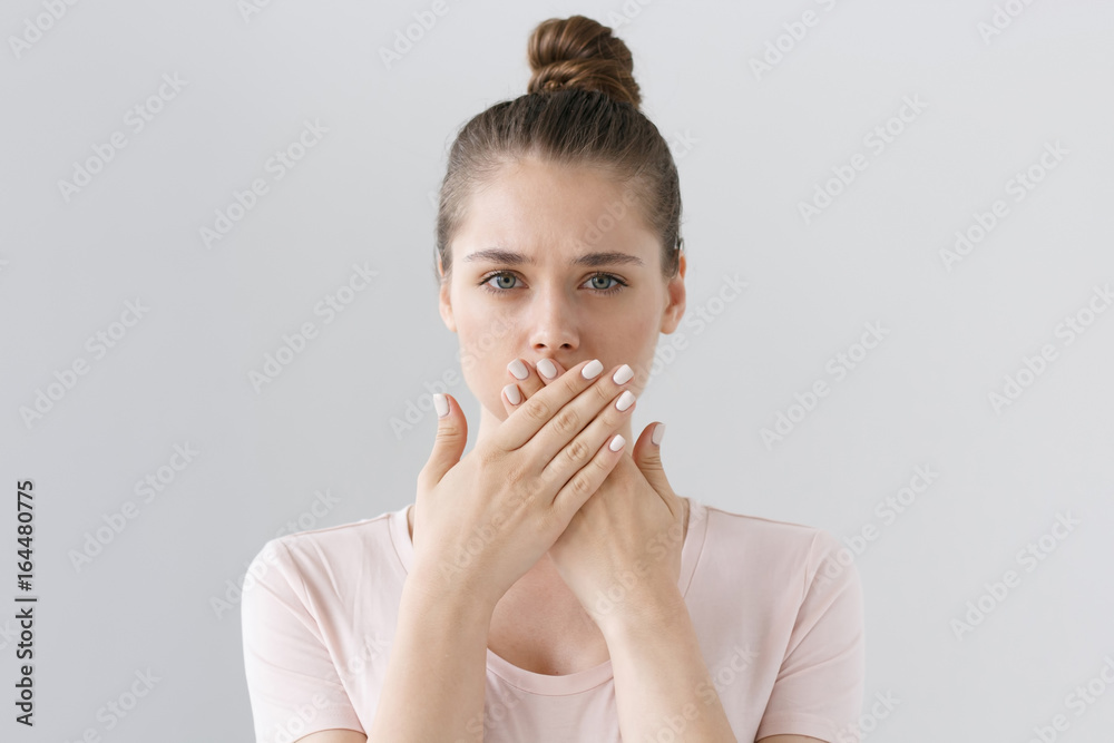 Fototapety, obrazy: Horizontal photo of young European female isolated on gray background with expression of secrecy and mistrust as she is covering mouth with two hands not willing to disclose something important.