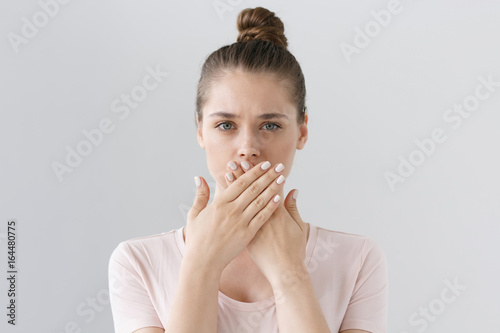 Valokuvatapetti Horizontal photo of young European female isolated on gray background with expression of secrecy and mistrust as she is covering mouth with two hands not willing to disclose something important