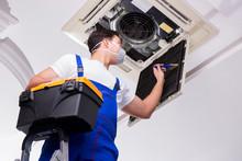Worker Repairing Ceiling Air C...