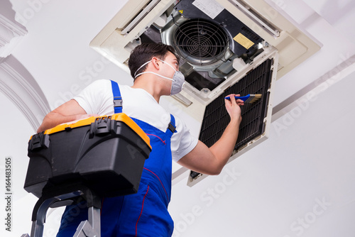 Fototapeta Worker repairing ceiling air conditioning unit obraz