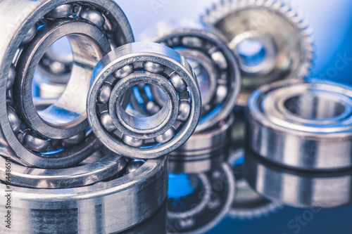 Photo Group of various ball bearings close up on nice blue background with reflections