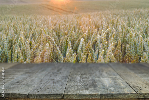 Fotobehang Zwavel geel wood board table in front of field of wheat on sunset light. Ready for product display montages