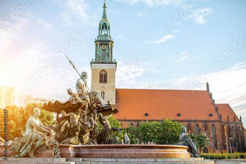 Morning view on Neptune fountain with saint Mary church in Berlin city Poster