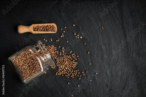 Fototapeta Seeds of coriander scattered on a stone black background. obraz
