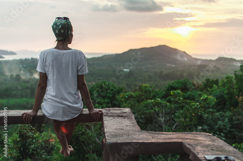 The view from the back of a woman sitting on a high and watching sunset