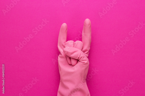 hand in pink protective glove shows horns gesture Wallpaper Mural