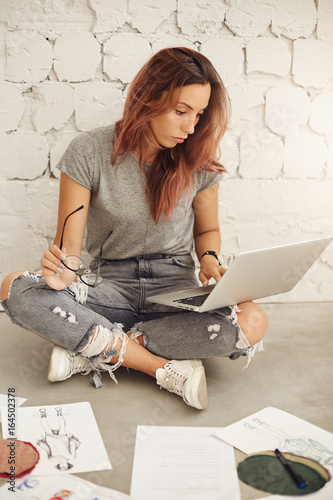 Fashion Designer Using Laptop Computer Surrounded By Textile And Sketches Sitting On Floor In Her Bright Sunny Studio Space Buy This Stock Photo And Explore Similar Images At Adobe Stock