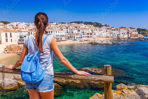 Foto op Canvas Barcelona Tourist woman in Calella de Palafrugell, Catalonia, Spain near of Barcelona. Scenic fisherman village with nice sand beach and clear blue water in nice bay. Famous resort destination in Costa Brava