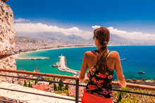 Woman Look On Landscape Of Alanya With Marina And Kizil Kule Red Tower In Antalya District, Turkey, Asia. Famous Tourist Destination With High Mountains. Summer Bright Day And Sea Shore