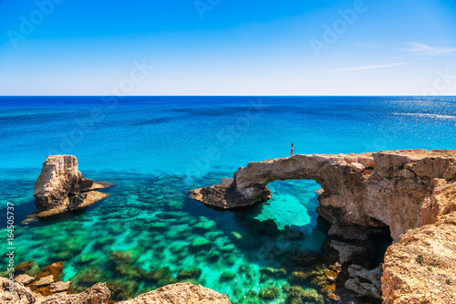 Garden Poster Cyprus Woman on the beautiful natural rock arch near of Ayia Napa, Cavo Greco and Protaras on Cyprus island, Mediterranean Sea. Legendary bridge lovers. Amazing blue green sea and sunny day.